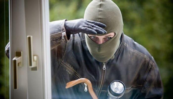 Грабитель смотрит через окно